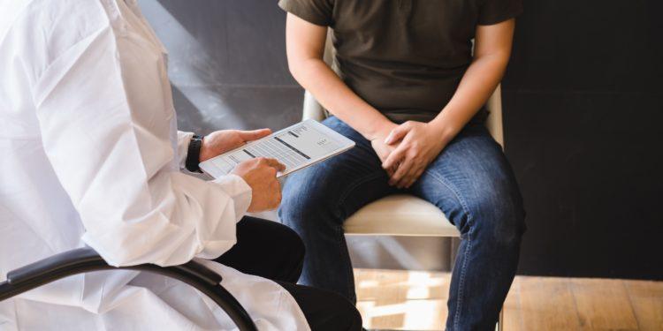 Arzt und Patient sitzen auf Stühlen und unterhalten sich
