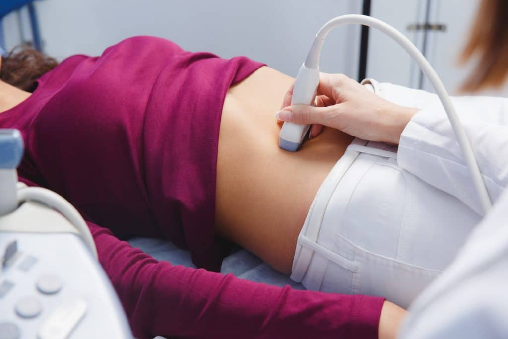 Ultraschalluntersuchung einer auf dem Rücken liegenden Frau