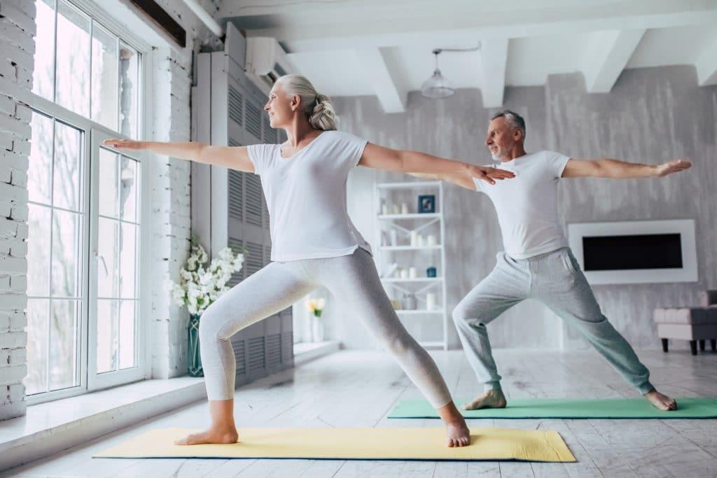 Ein älteres Paar macht Yoga daheim