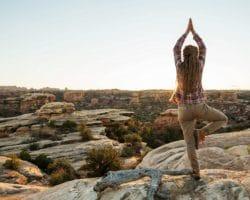 Frau macht Yoga auf einem Berg