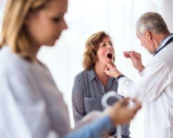 Ein älterer Arzt untersucht den Mundraum einer Patientin