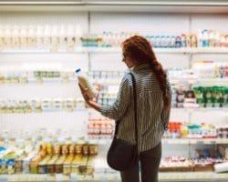 Junge Frau steht vor Kühlregal im Supermarkt und betrachtet Milchflasche in ihrer Hand