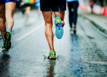 Die Beine mehrere Personen von hinten beim Laufen auf einer nassen Straße