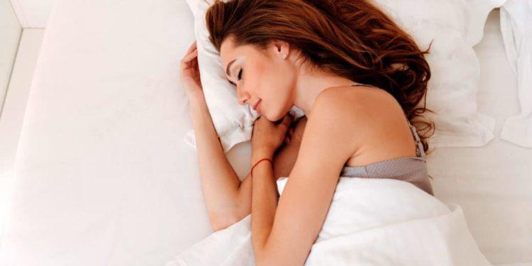 Junge Frau liegt schlafend im Bett