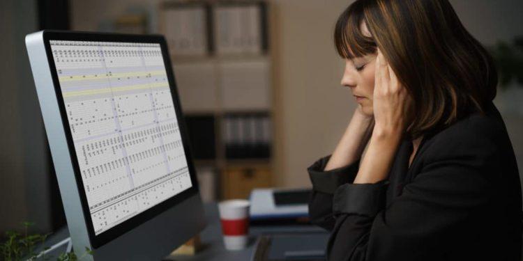 Am Bildschirm arbeitende Frau massiert sich die Schläfen