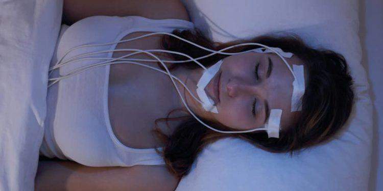 Eine schlafende Frau liegt in einem Bett und ist mit Elektroden verkabelt.