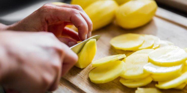 Mann schneidet Kartoffeln in Scheiben