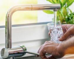 Mann füllt Wasser aus dem Wasserhahn in ein Glas