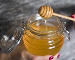 Frau hält ein Glas Honig und einen Honigheber in den Händen
