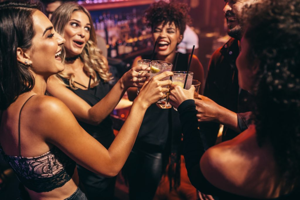 A group of young people toast in a nightclub