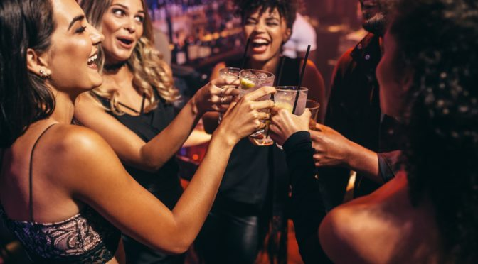 Eine Gruppe junger Personen stoßen in einem Nachtclub an