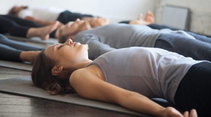 mehrere Personen entspannen in einem Fitnesskurs mit geschlossenen Augen auf dem Boden