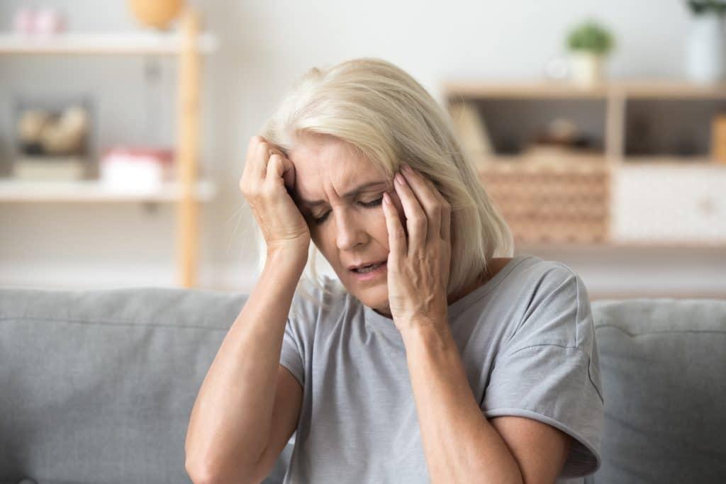 Frau mittleren Alters fasst sich mit beiden Händen ins Gesicht und an den Kopf