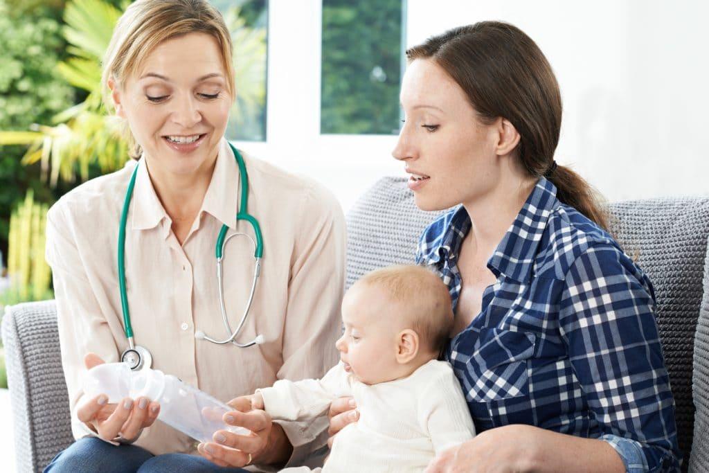 Gesundheitsschwester gibt Mutter mit Baby auf dem Schoß Ratschläge