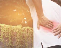 Rückaufnahme eines Mannes, der sich an den schmerzenden Rücken fasst