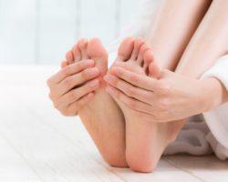 Füße einer Frau, die im Bademantel auf dem Boden sitzt und Ihre Fußsohlen anfässt