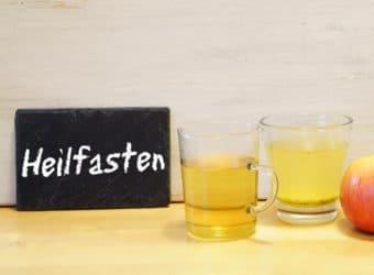 """2 gefüllte Gläser, ein Apfel und eine Schiefertafel mit der Aufschrift """"Heilfasten"""""""