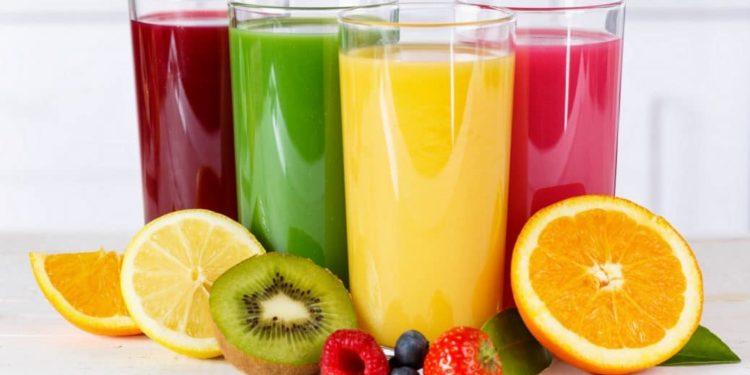 4 Gläser mit Säften in unterschiedlichen Farben und Obst
