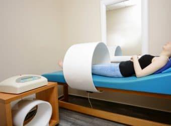 Junge Frau liegt und bekommt eine Magnetfeldtherapie
