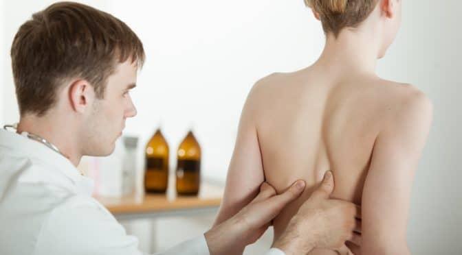 Arzt tastet Rücken eines Jungen ab