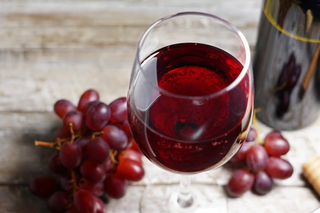 Rote Trauben und ein Glas Rotwein auf einem Holztisch