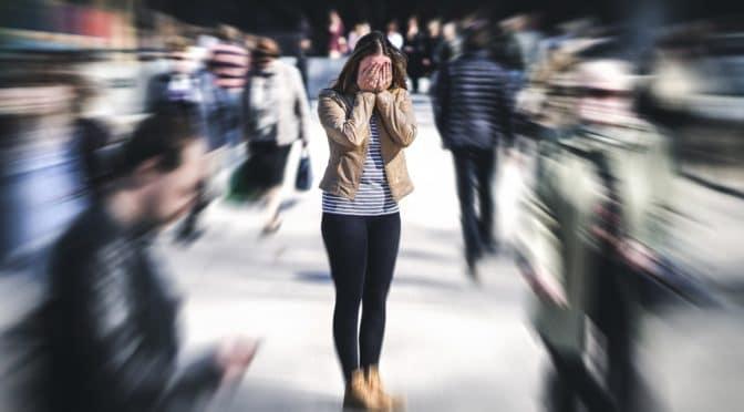 Fokussierung einer Frau, die in einer Menge steht und sich die Hände vor das Gesicht hält