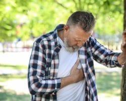 Mann mittleren Alters stützt sich an einen Baum und fasst sich ans Herz