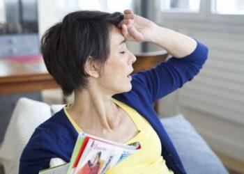 Frau mittleren Alters fasst sich mit geschlossenen Augen an die Stirn