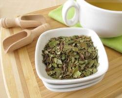 Bärentraubenblätter in einer Schale und eine Tasse Tee