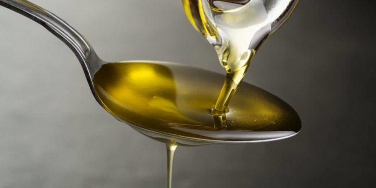 Olivenöl läuft aus einer Glasflasche auf einen Teelöffel