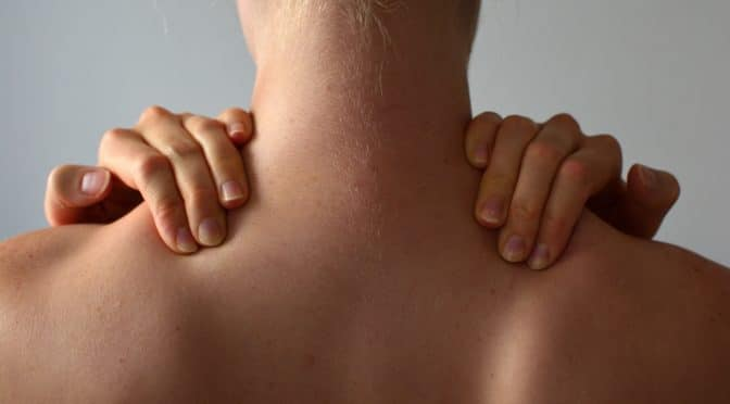 Frau von hinten fasst sich an die Nackenmuskulatur