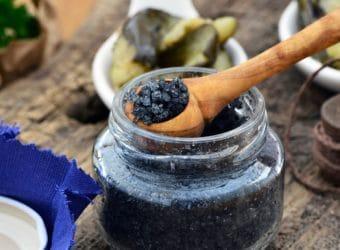 Holzlöffel hebt schwarzes Salz aus Glas