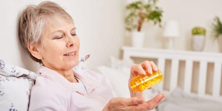 Ältere Frau sitzt auf Bett und kippt Medikamente auf Ihre Hand