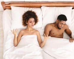 Junges Paar liegt im Bett, Frau hebt Hände fragend, Mann schaut an sich unter der Bettdecke herunter
