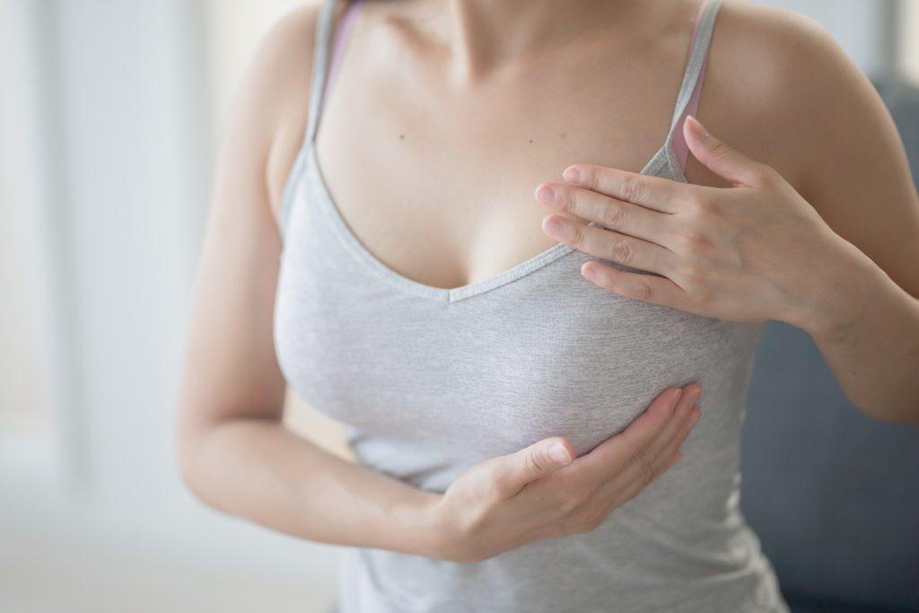 Frau im grauen Top tastet ihre Brust ab