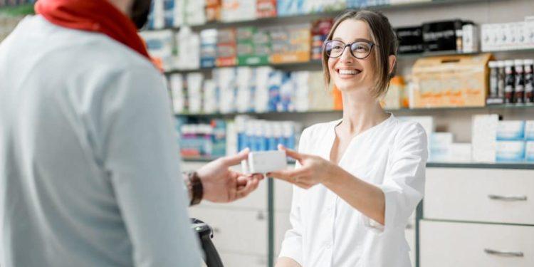 Lächelnde Apothekerin bedient einen Mann