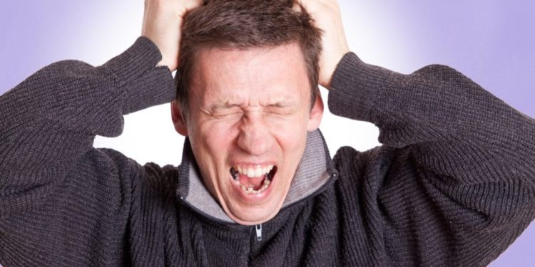 Mann schreit und fasst sich an den Kopf