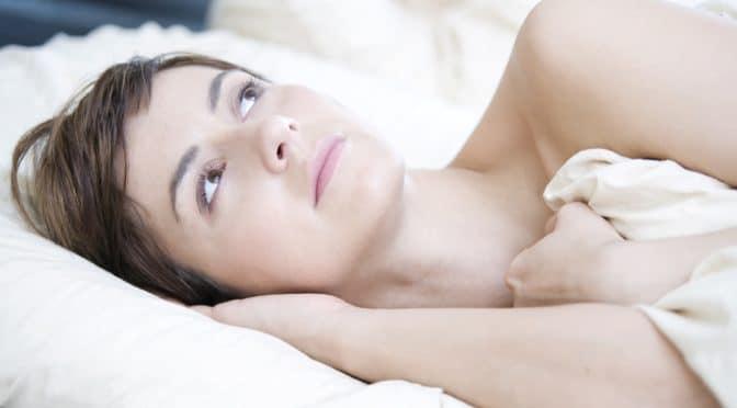 Junge Frau liegt mit geöffneten Augen im Bett