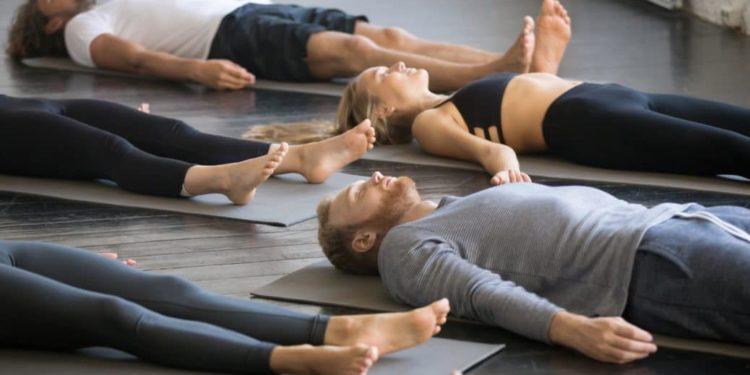 Mehrere Leute liegen entspannt in einem Sportkurs auf dem Boden