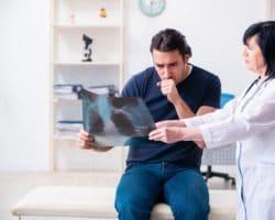 Ärztin zeigt einem hustenden Patienten eine Röntgenaufnahme