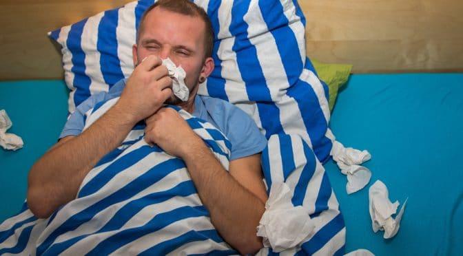 Mann liegt erkältet im Bett