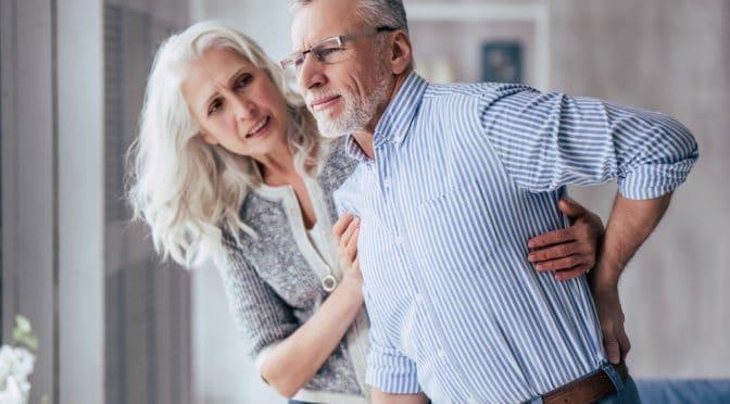 Frau stützt Mann mit Wirbelsäulenschmerzen
