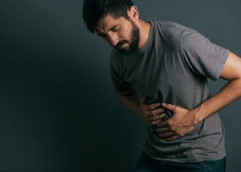 Junger Mann fasst sich an den schmerzenden Bauch