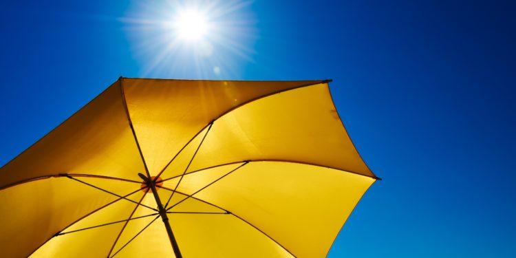 Gelber Sonnenschirm von unten mit Blick zum blauen Himmel