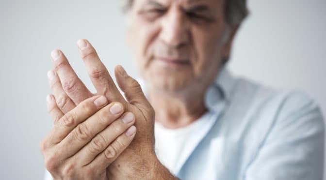 Ein Mann fasst sich an die schmerzende Hand