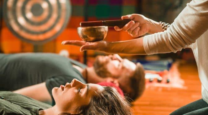 Mann und Frau liegen auf dem Boden und erhalten Klangtherapie