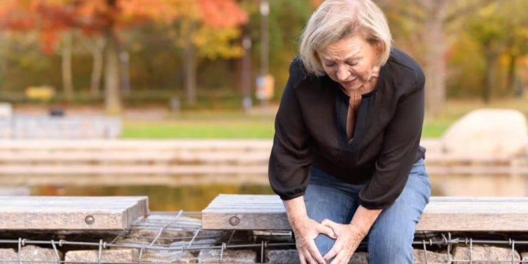 Ältere Frau sitzt auf Bank und fasst sich ans Knie