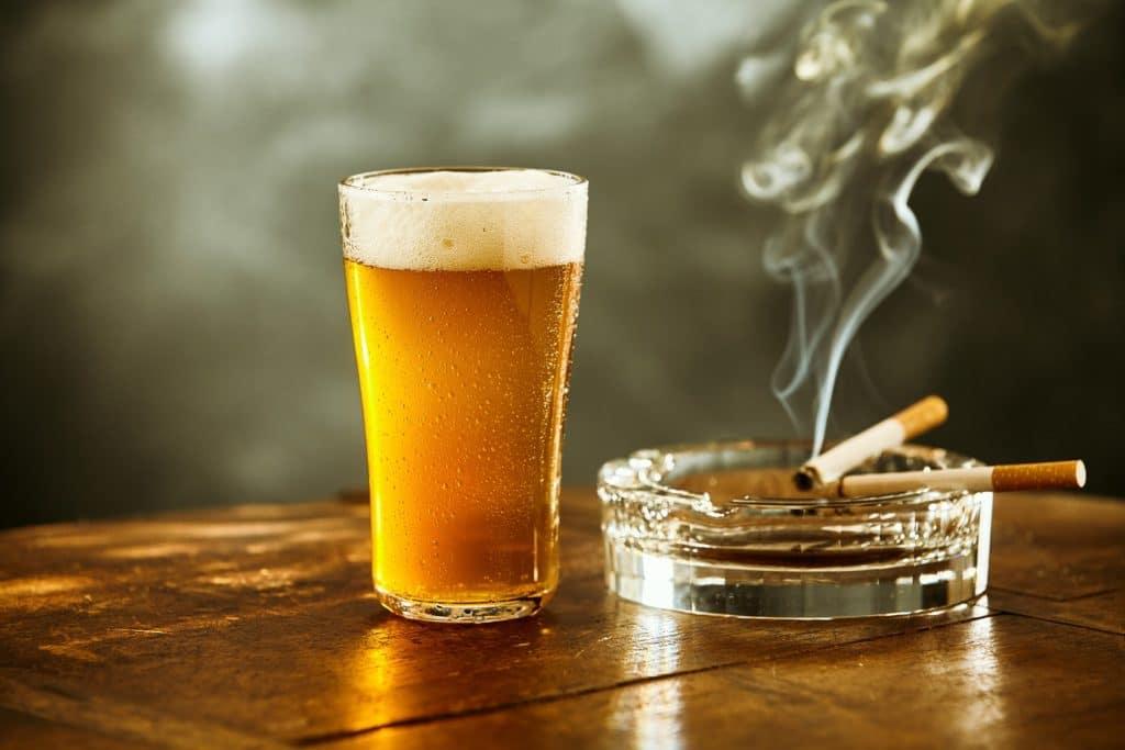 Volles Glas Bier und und brennende Zigaretten im Aschenbecher