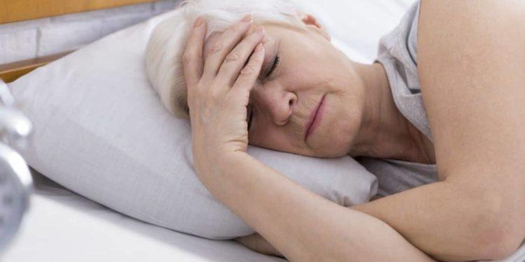 Ältere Frau liegt müde im Bett