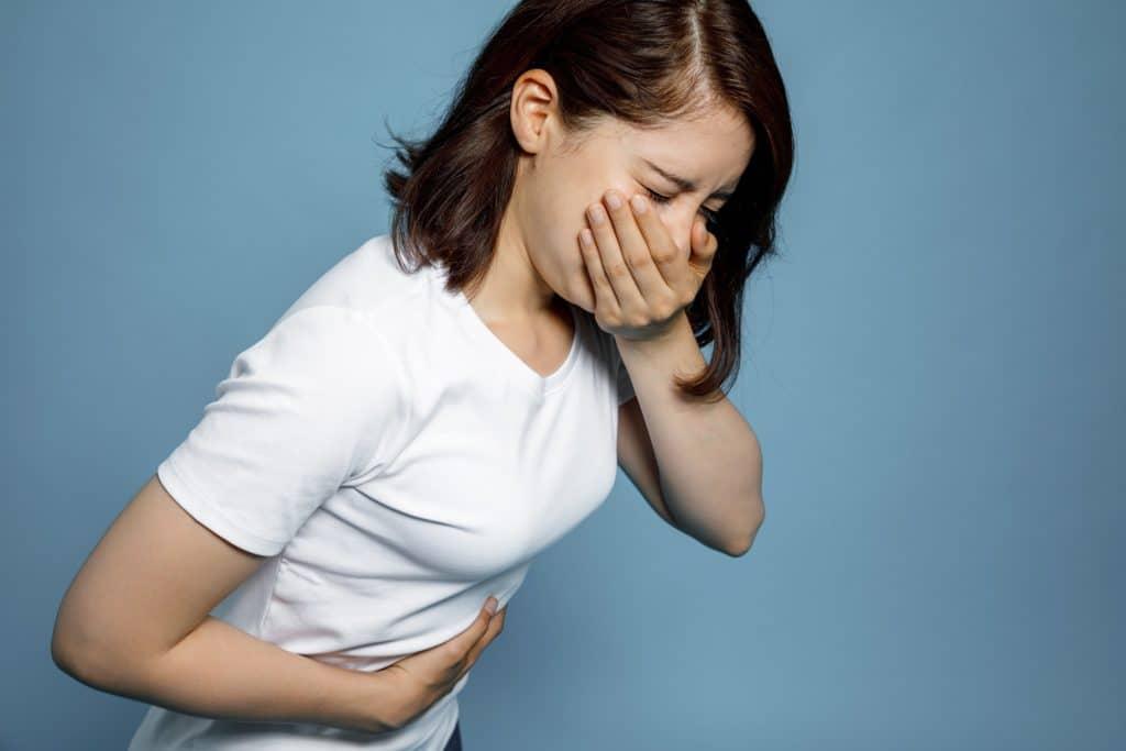 Frau mit Überlkeit und Bauchschmerzen